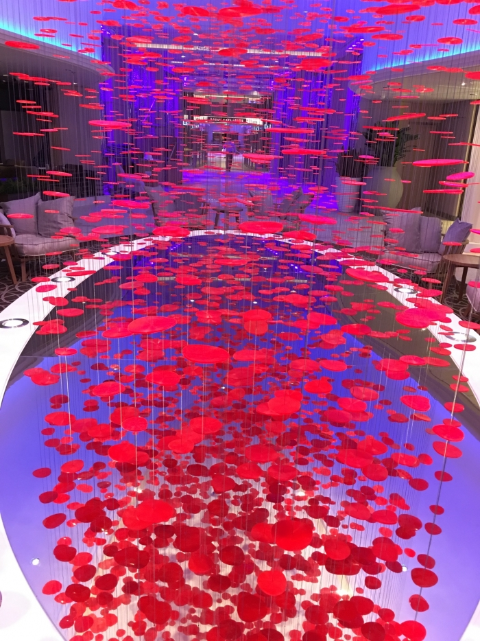 "Lure - Bieli Liu, a Chinese artist played into the natural movement of Ovation of the Seas with an adaptation from her ""Lure"" series of installations. The sculpture was created to fit the rotunda location and represents an ancient Chinese legend depicting the red threads that connect Chinese children to their soulmates. A disc may be connected to another, as a pair; and a pair of disks may sprout from a single thread. The installation is designed to suspend from the ceiling forming a vibrant and energetic piece that responds to subtle air currents and movement as the red coils turn, and strands of thread become entangled."