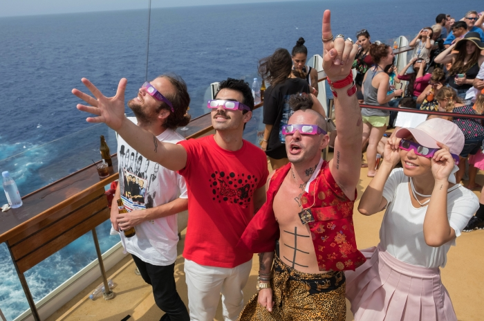 "Jack Lawless, Joe Jonas, Cole Whittle and JinJoo of multi-platinum-selling band DNCE watched the Great American Eclipse aboard Royal Caribbean's Oasis of the Seas, Mon., Aug. 21. The ship set sail along the path of totality, offering DNCE and fellow passengers an unobstructed view at sea. DNCE accompanied legendary songstress Bonnie Tyler in an exclusive performance of her '80s hit, ""Total Eclipse of the Heart,"" as a part of the cruise line's Total Eclipse Cruise."