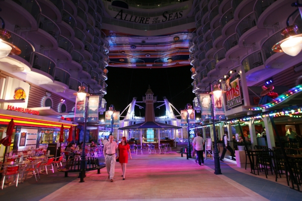 Allure of the Seas Boardwalk neighborhood lights up at night.